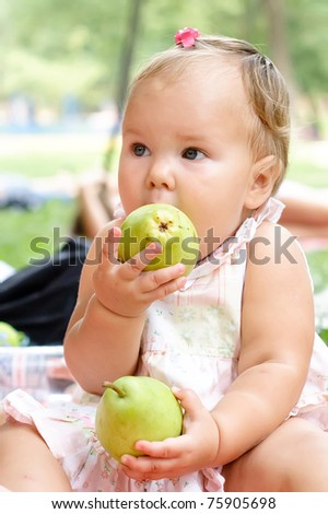 Hungry beautiful baby eating a pear