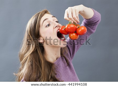 hungry beautiful young girl holding and eating up a tomato grape with appetite and greed for healthy vegetarian diet and nutrition, indoors - stock photo
