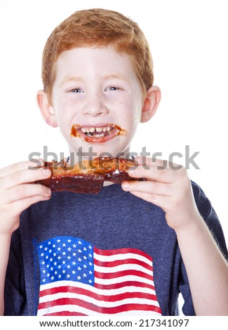 Hungry boy eating BBQ rib in studio