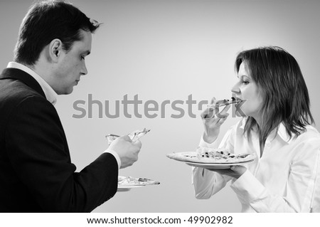 hungry business man and woman eating - stock photo