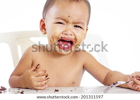 Hungry crying little boy asking for more cake.