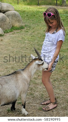 Hungry goat and teenager - stock photo