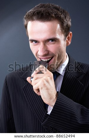 Hungry handsome businessman, male model, biting or eating mobile phone and smiling - head shot made in studio on dark background - stock photo
