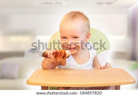 Hungry little  boy eat chicken. Yummy but harmful