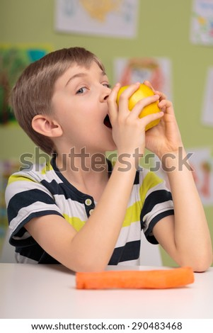 Hungry little child eating delicious apple - stock photo