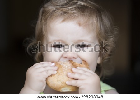 Hungry little cute baby boy with blonde curly hair holding and biting fresh delicious bread roll on black backdroung, horizontal picture - stock photo