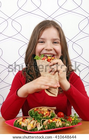 hungry little girl eat burritos - stock photo