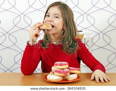 hungry little girl eat sweet donuts - stock photo