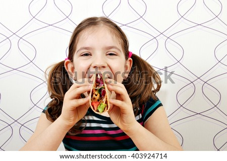hungry little girl eating tacos - stock photo