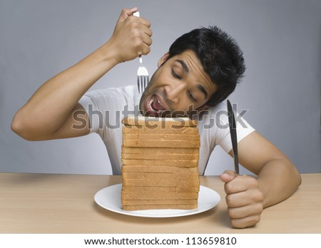Hungry man eating slices of bread - stock photo