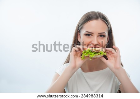 Hungry pretty woman is biting hamburger gradually. She is looking at the camera malevolently. Isolated on a white background. There is copy space in the left side - stock photo