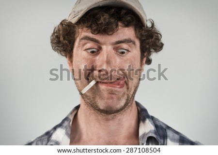 Hungry redneck licks his lips while smoking a cigarette