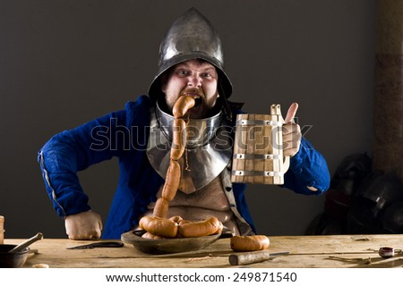Hungry warrior in medieval tavern - stock photo