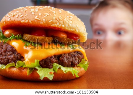 Hungry young boy is staring beef burger on table - stock photo