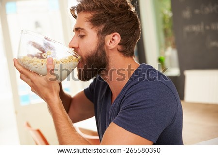 Hungry Young Man Eating Breakfast From Glass Bowl - stock photo