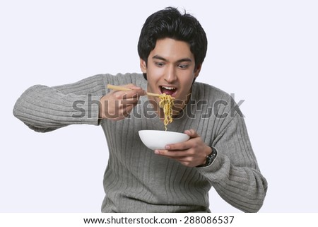 Hungry young man eating noodles