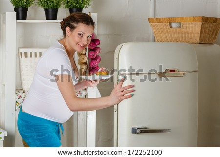 Hungry young pregnant woman stands near refrigerator and searches the food. - stock photo