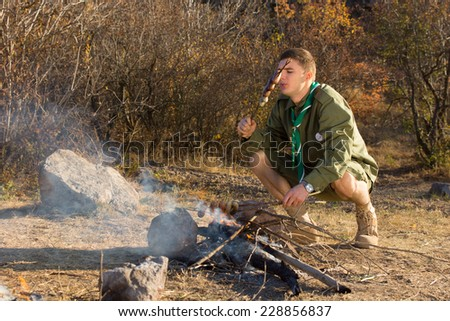 Hungry young scout cooking sausages over a small open fire in a clearing as he explores the wilderness