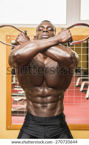 Hunky muscular black bodybuilder working out in gym, exercising back with dumbbells - stock photo