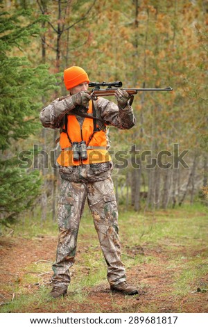 hunter aiming deer rifle in forest
