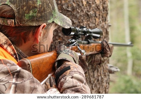 hunter aiming rifle in forest