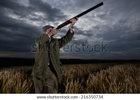 Hunter aiming rifle towards sky in wheat field - stock photo