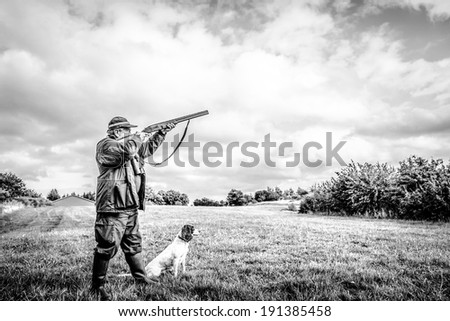 Hunter aiming with his rifle - stock photo
