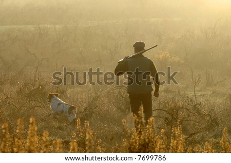 hunter and his dog looking for small game - stock photo