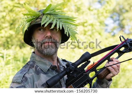 Hunter holding a crossbow while in the woods. - stock photo