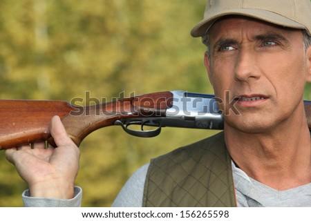 Hunter holding his shotgun over his shoulders - stock photo