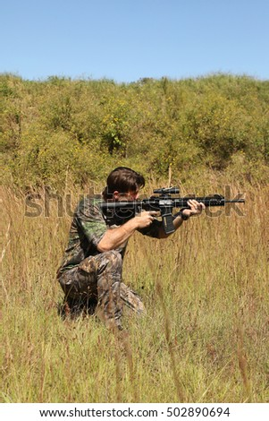 Hunter in grassy field with military rifle looking through scope at target
