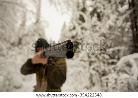 Hunter is pointing a gun to unseen aim during the hunt in winter forest. - stock photo