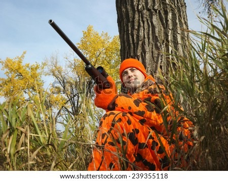 Hunter Leaning Against Tree - stock photo