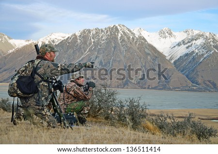 Hunter looking for Himalayan tahr in the Southern Alps of New Zealand - stock photo