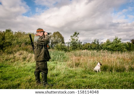 Hunter looking through binculars assisted by his dog - stock photo