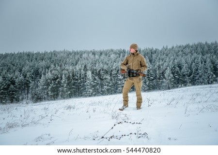 Hunter man dressed in camouflage clothing  in the winter pine forest. Armed with a rifle