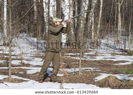 Hunter man with old 16 caliber side-by-side double-barreled shotgun dressed in dark khaki clothing in the forest