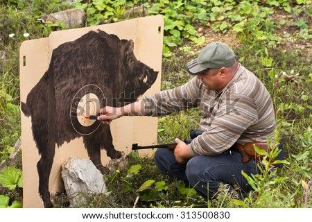 hunter marking traces from shots on target - stock photo