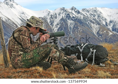 Hunter scoping for Himalayan tahr in the Southern Alps of New Zealand - stock photo