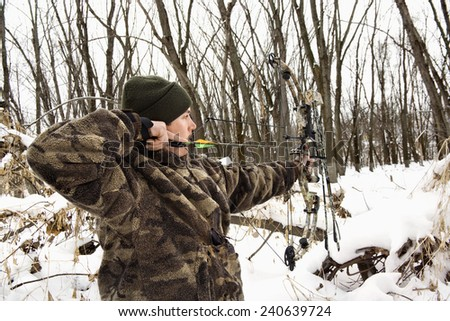 Hunter Shooting Bow and Arrow in Snow - stock photo