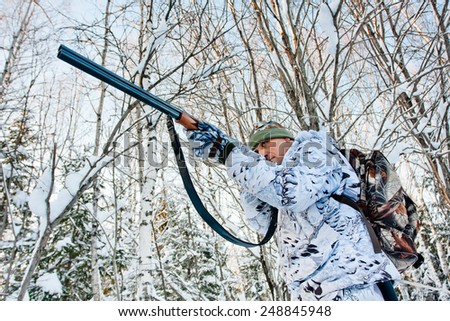 hunter shooting in the forest in winter - stock photo