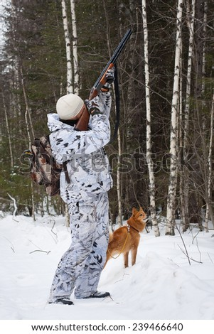 hunter shooting in winter forest - stock photo