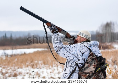 hunter shooting on the snowy field  - stock photo