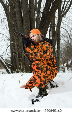 Hunter Shooting Rifle in Snow - stock photo