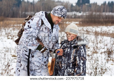 hunter shows his son how to charge the gun - stock photo