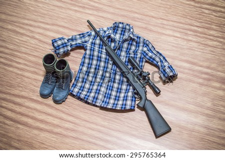 hunter uniform for toy man scale on wood floor backgrounds - stock photo
