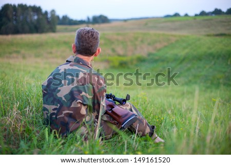 Hunter waiting silently for the hunt during the hunting season - stock photo