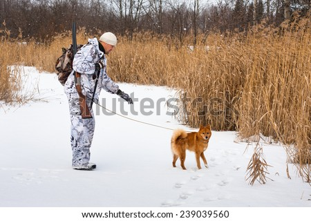 hunter with a dog on a frozen lake  - stock photo