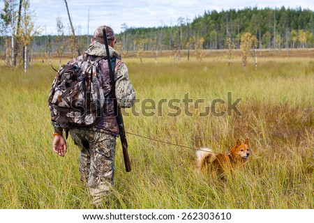 hunter with dog on the swamp - stock photo