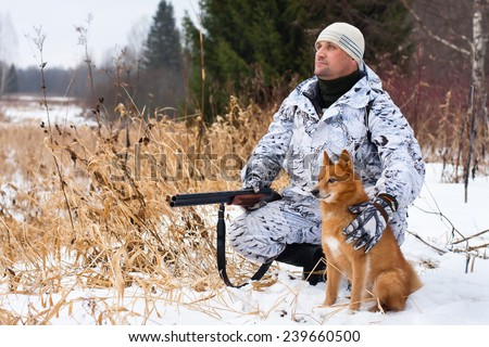 hunter with gun and dog in winter - stock photo